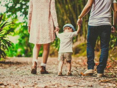 low-angle-shot-of-a-child-held-by-woman-and-man-on-on-each-3038455-e1593043051702